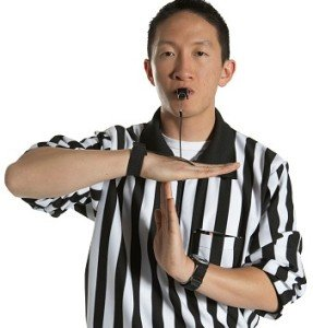 Young male referee blowing whistle, signaling for time out, portrait